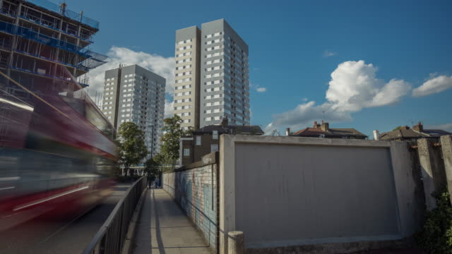 white clouds against a blue sky move rapidly pass two residential council tower blocks and a new private development under construction as local traffic and pedestrians move over a railway bridge in the foreground - wall building feature stock videos & royalty-free footage