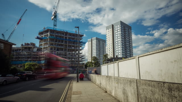 White clouds against a blue sky move rapidly pass two residential council tower blocks and a new private development under construction as local traffic and pedestrians move over a railway bridge in the foreground