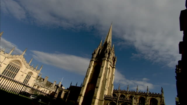 white clouds drift above the towers of the university of oxford. - turmspitze stock-videos und b-roll-filmmaterial