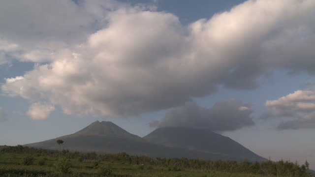 white clouds float above twin volcanic peaks in volcanoes national park. available in hd. - hd format stock videos & royalty-free footage