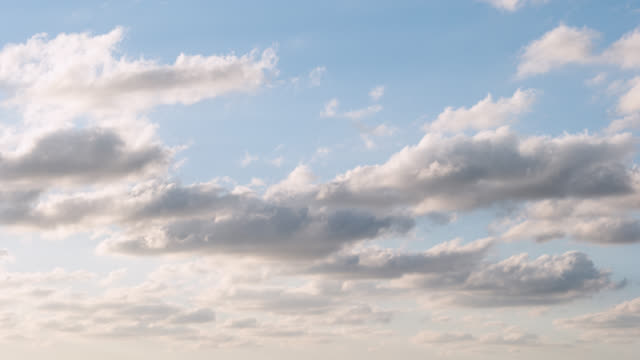 vidéos et rushes de white clouds in a blue sky captured in an afternoon - ciel sans nuage