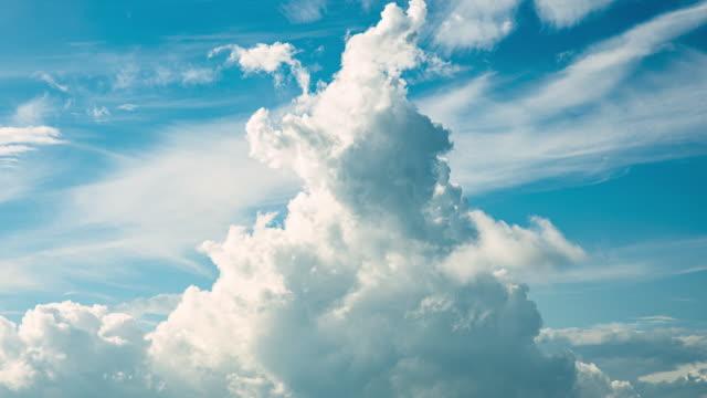 vidéos et rushes de white clouds in a blue sky (time lapse) - cumulonimbus