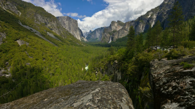 time lapse wide crane shot white clouds in blue sky and shadows over el capitan and bridalveil fall with large rocks in foreground - californian sierra nevada stock videos & royalty-free footage