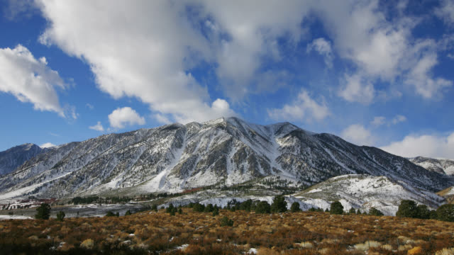 TIME LAPSE WIDE SHOT white clouds in blue sky over eastern side of snowy Sierra Nevada range, California