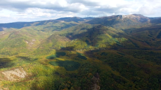 aerial: white clouds over colorful forest on mountain ridges - chiaroscuro stock videos and b-roll footage