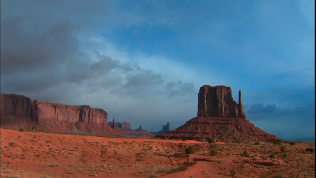 vidéos et rushes de white clouds pass above rock formations in monument valley. - piton rocheux
