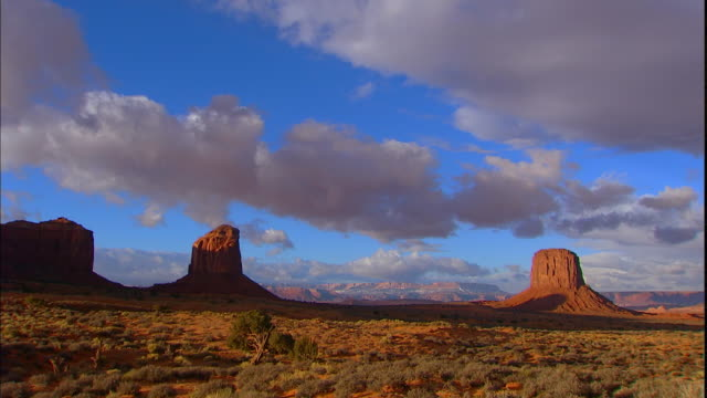 vídeos y material grabado en eventos de stock de white clouds pass above rock formations in monument valley. - arizona