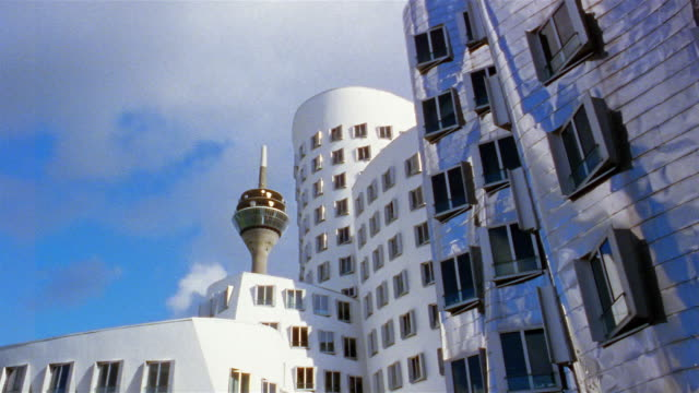 white clouds pass over modern office buildings in the der neue zollhof complex in dusseldorf, germany. - デュッセルドルフ点の映像素材/bロール