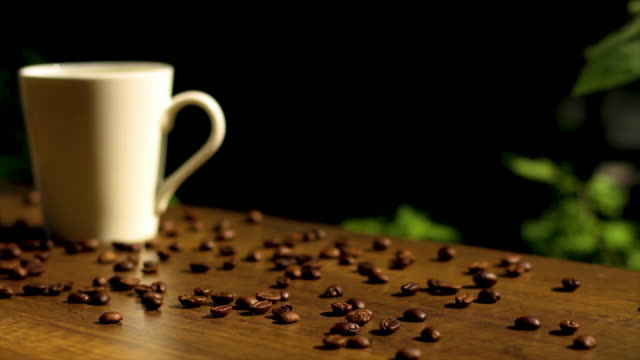 white coffee cup and roasted coffee beans on wooden table with sunlight, panning and dolly shot - coffee table stock videos & royalty-free footage