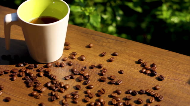 White Coffee Cup and Roasted Coffee Beans on wooden table with sunlight, panning shot and dolly shot