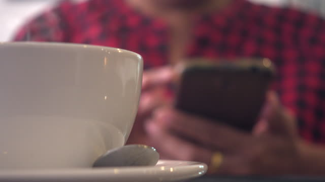 white coffee cup with blur woman use smart phone - differential focus stock videos & royalty-free footage