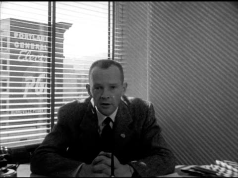 white collar worker tom jones sitting at desk near window talking about family job lumber company voting for dwight eisenhower for 1952 us... - white collar worker点の映像素材/bロール