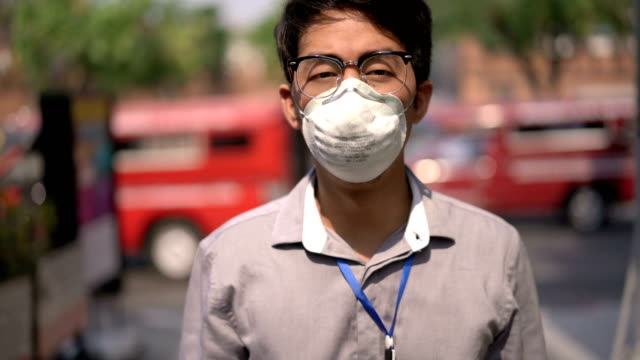 white collar worker wearing air pollution mask while walking to camera on busy traffic - asian man coughing stock videos & royalty-free footage