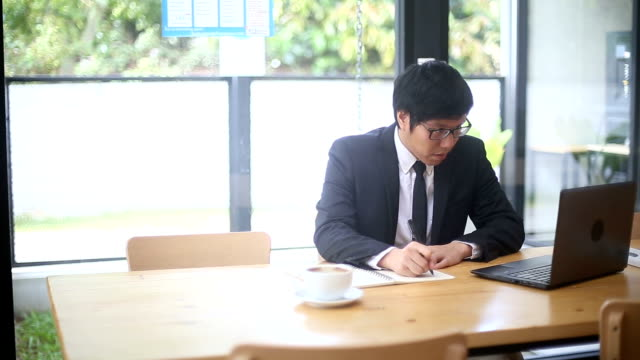 論文を書くメモ中のラップトップに取り組んでホワイト カラー労働者 - white collar worker点の映像素材/bロール