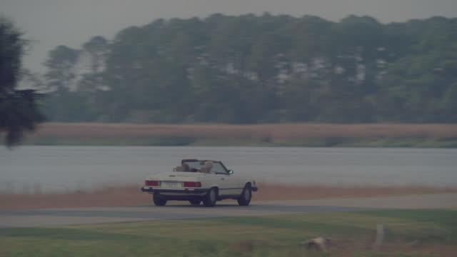 TS White convertible driving on white picket bridge over river / Tybee Island, Georgia, United States
