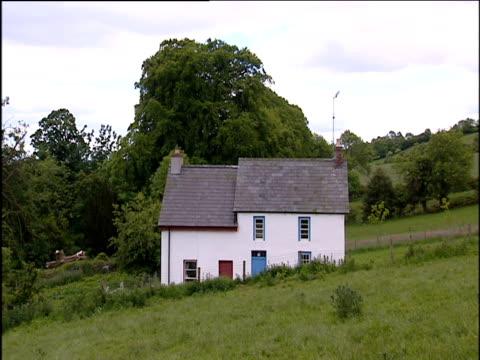 vídeos de stock, filmes e b-roll de white cottage on hillside as car drives past; northern ireland - província de ulster