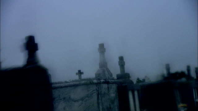 A white cross accents the top of a large tombstone in a cemetery. Available in HD.