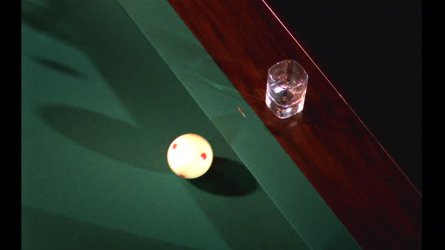 a white cue ball bounces off the side of a pool table propelling a coin to flip in slow-motion and land in the glass. - cue ball stock videos & royalty-free footage
