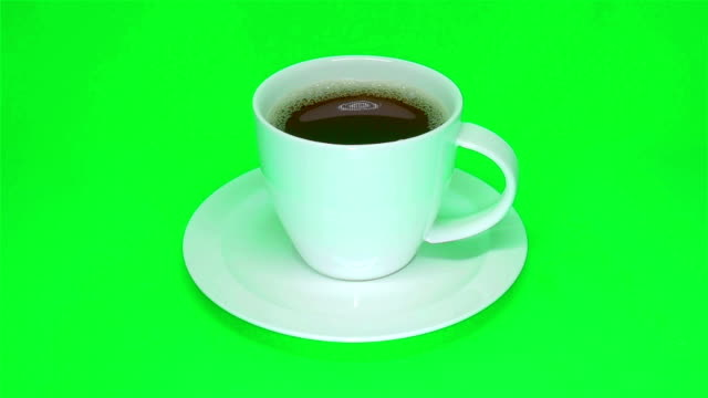 white cup of coffee moves on a green background. - coffee cup stock videos & royalty-free footage