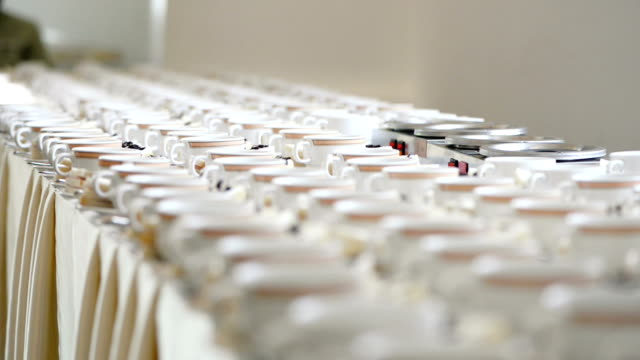 White Cups With Saucers And Teaspoons Are On Table In Several Rows At Banquet