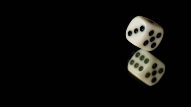slo mo ld white die rolling on black table - dice stock videos & royalty-free footage
