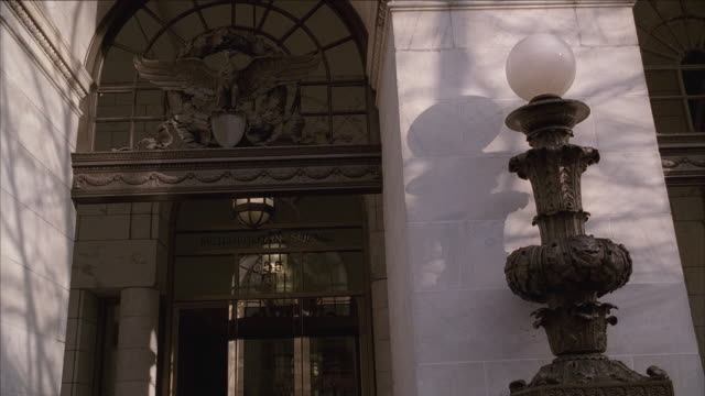 la white dome-shaped bulb resting atop ornamental base by doorway of eagle building, bulb and base casting shadow on building, pedestrian passing by / washington, d.c., united states - architrav stock-videos und b-roll-filmmaterial