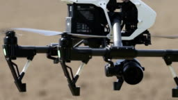 White drone flying on agricultural field background, drone on blured background