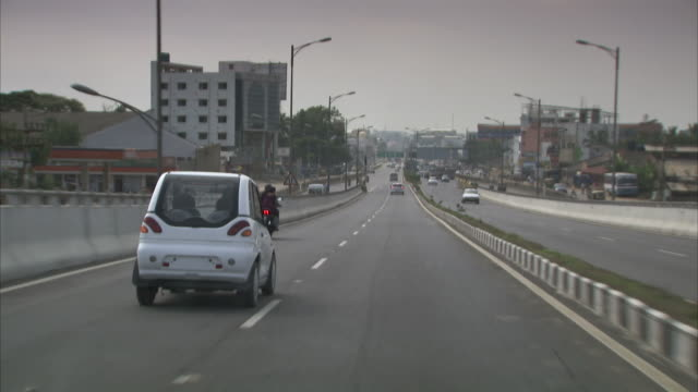 a white electric car moves along the freeway in bangalore, india. - bangalore stock videos and b-roll footage