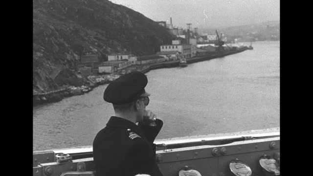 White ensign flying / destroyer in BG / personal standard of Princess Elizabeth flying / Duke of Edinburgh in sunglasses and officers looking out as...