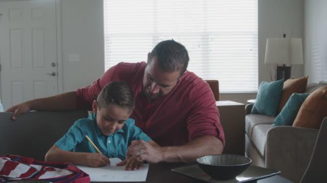 vídeos de stock, filmes e b-roll de um pai branco auxilia seu filho com a lição de casa - matemática opção educacional