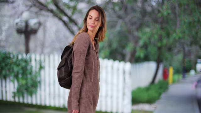 stockvideo's en b-roll-footage met white female millennial with backpack, waiting on lawn in late afternoon - tuinhek