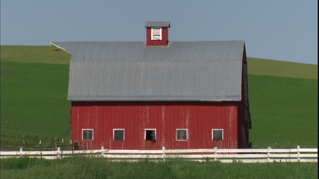 A white fence surrounds a red barn on a farm.