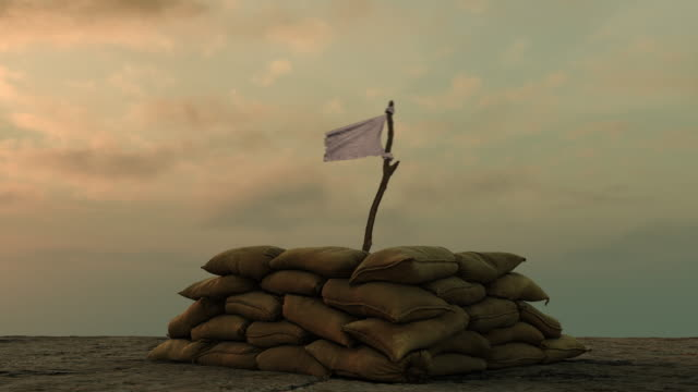 white flag behind military sand bags against sullen sky - surrendering stock videos & royalty-free footage