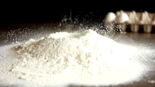vídeos de stock, filmes e b-roll de a farinha branca derramou no fundo preto - neve seca e solta