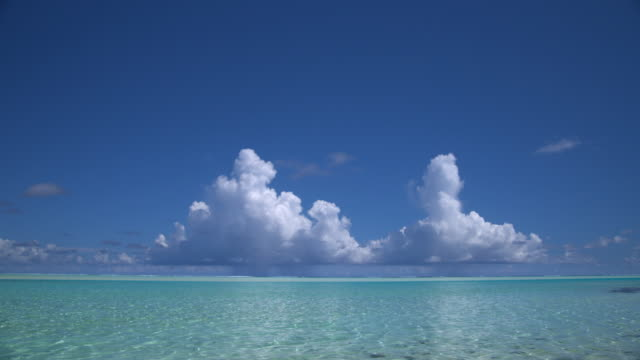 WS, White fluffy clouds above tropical water, Aitutaki Lagoon, Aitutaki, Cook Islands