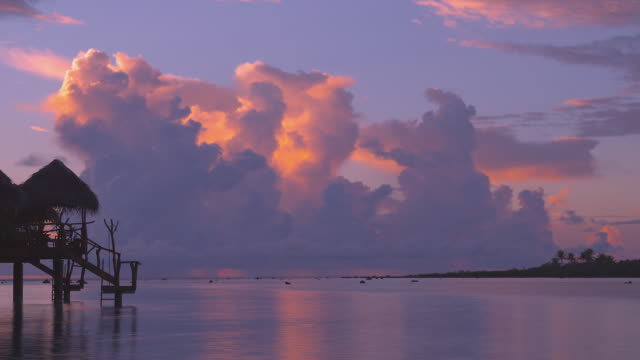 t/l, ws, white fluffy clouds above tropical water at sunrise, silhouette of overwater bungalow in foreground, aitutaki lagoon, aitutaki, cook islands - aitutaki lagoon stock videos & royalty-free footage