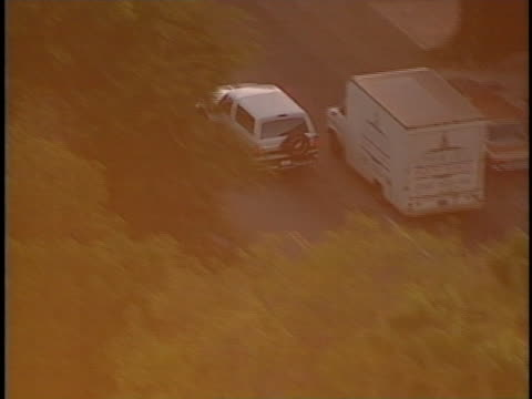 white ford bronco carrying o.j. simpson weaves through traffic during a police chase. - o・j・シンプソン点の映像素材/bロール