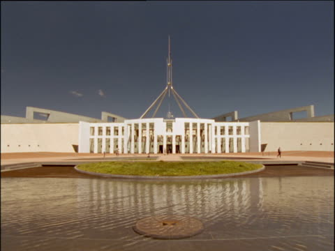 white front of australian parliament building behind rippling pond canberra - canberra stock videos & royalty-free footage