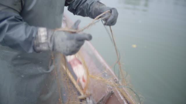 白い髪の漁師をキャッチでネットの引き出し - 男漁師点の映像素材/bロール