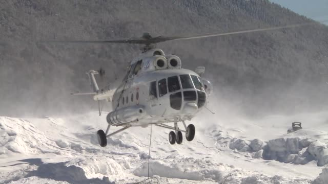white helicopter taking off from snowy helipad / helicopter flying away past mountain range helicopter taking off from russian ski resort on march 17... - ski flying stock videos and b-roll footage