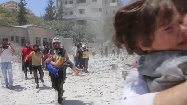 vídeos de stock e filmes b-roll de white helmets civil defense agency members search and rescue survivors from the rubble of buildings following the attacks by syrian regime and... - ataque aéreo