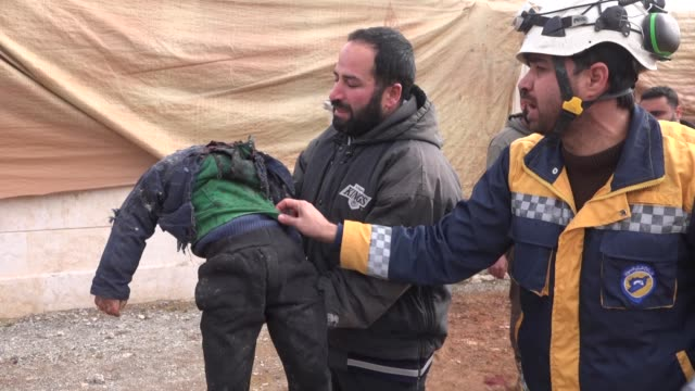 vídeos de stock e filmes b-roll de white helmets members and syrian civilians carry dead bodies into vehicles and transport them to a burial site after regime warplanes targeted a... - ataque aéreo