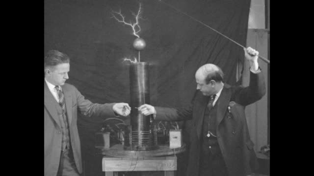 vs h c white holds a baton that's zapped by a tesla coil he holds up an incandescent bulb that lights up white and his assistants demonstrate various... - tesla coil stock videos and b-roll footage