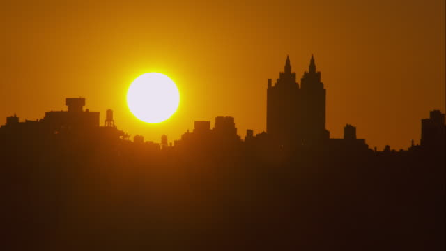 white hot sun slowly rising above new york city skyline - upper west side manhattan stock videos and b-roll footage
