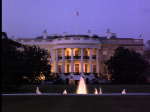 White House at dusk with fountain in foreground + Christmas decorations / Washington DC