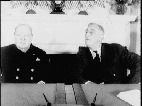 White House / British Prime Minister Winston Churchill and FDR speak at table / Churchill and Roosevelt sitting at a desk smiling and talking /...