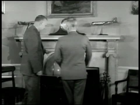 White House building INT WS Secretary of State General George C Marshall w/ President Harry S Truman looking at globe CU Marshall listening MS...