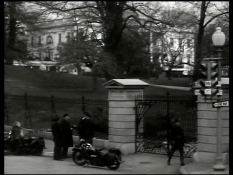 White House gates w/ motorcycle police parked standing on sidewalk talking Press w/ White House Press Secretary Stephen T Early in office CU Headline...