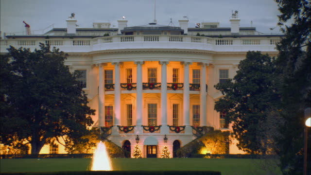 ms white house illuminating with spotlights and decorated with holiday wreaths / washington, d.c., united states - white house washington dc stock videos and b-roll footage