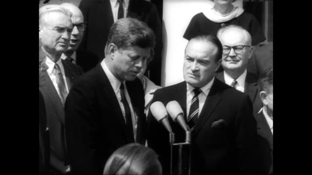 vídeos de stock e filmes b-roll de ext white house / int president john f kennedy stands next to bob hope at podium surrounded by congressional members and press / president kennedy... - bob hope comediante